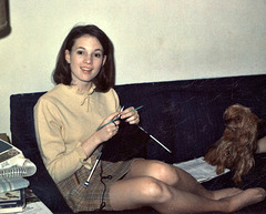 Young woman knitting with dog, 1968