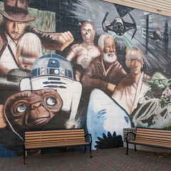 Nostalgia of these benches' cinderblocks mural of 70s-80s movies.