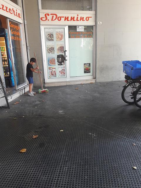 Il ragazzino con le scuole chiuse toglieva le foglie sotto il portico..era molto impegnato e bravo!