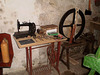 Old sewing machine and spinning wheel.
