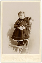 Girl Holding Photo and Standing on Chair