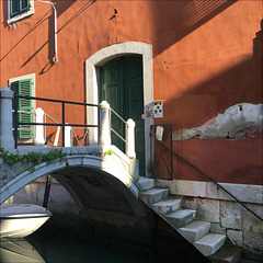 A bridge in front of the door, a stair into the water.