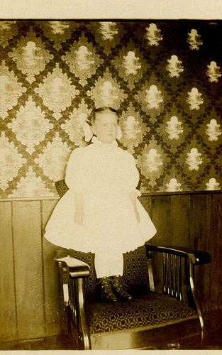 Girl Standing on a Chair in Front of Patterned Wallpaper