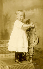 Erma Herr Standing on a Wicker Chair
