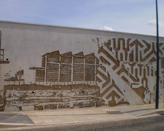 Industrial scenery in Vhils' mural.