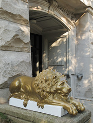 Freshly-painted golden lion on a freshly-painted white base.