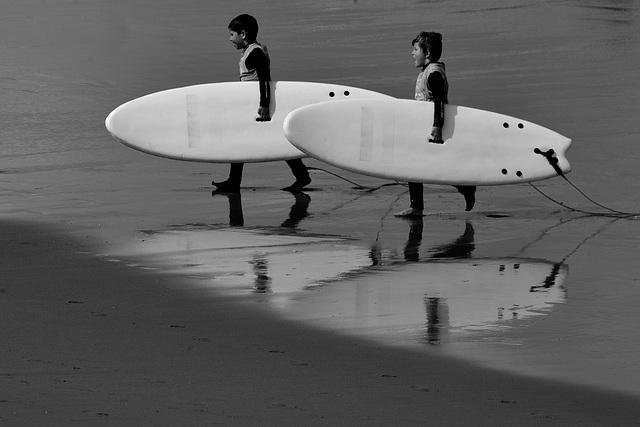 Niños con la tabla de surf bajo el brazo
